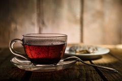Cup of tea. Glass cup of black tea, teaspoon and honey cake on wooden table Royalty Free Stock Photos