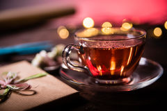 Cup of tea. Glass cup of fruity tea, teaspoon, wrapped gift and christmas lights on wooden table. Christmas concept Stock Photography