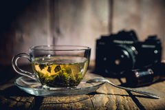 Cup of tea. Glass cup of green tea, teaspoon and blacj analog camera on wooden table Stock Photos