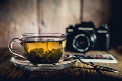 Cup of tea. Glass cup of green tea, teaspoon and black analog camera on wooden table, pictures Stock Image