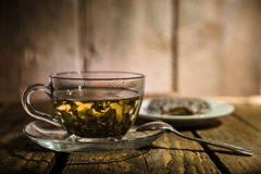 Cup of tea. Glass cup of green tea, teaspoon and honey cake on wooden table Stock Photo