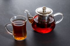 Cup of tea with glass teapot on the black background. Side view Royalty Free Stock Photos