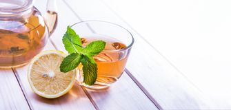 Cup of tea, glass teapot, mint and lemon on wooden table royalty free stock photography