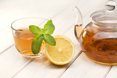 Cup of tea, glass teapot, mint and lemon on stock image