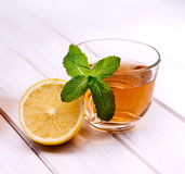 Cup of tea, glass teapot, mint and lemon on wooden table stock photo