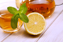 Cup of tea, glass teapot, mint and lemon on wooden table royalty free stock photo