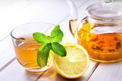 Cup of tea, glass teapot, mint and lemon on a wooden table stock images