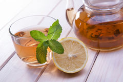Cup of tea, glass teapot, mint and lemon on wooden table stock photography