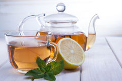 Cup of tea, glass teapot, mint and lemon on wooden table stock images