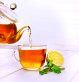 Cup of tea, glass teapot, mint and lemon on wooden table Royalty Free Stock Image