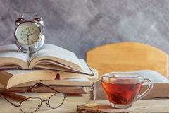 A cup of tea with glasses and  alarm clock on stack books Stock Photos