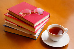 Cup of tea, glasses and stack of books Royalty Free Stock Images
