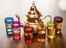 Arabic teapot with colorful glasses. Cup of tea and glasses of various colors with n dark background Stock Images