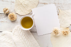 Cup of tea with gloves, flowers and blank card on white wooden background Royalty Free Stock Photos