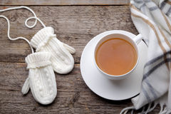 Cup of tea with gloves Stock Photos