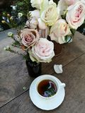 A cup of tea with Gorgeous bouquet of fresh roses on the table in the garden. Image royalty free stock photo