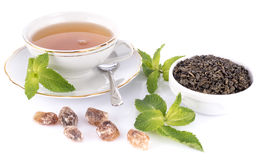 Cup of tea with green dry tea and crystal sugar Royalty Free Stock Photos