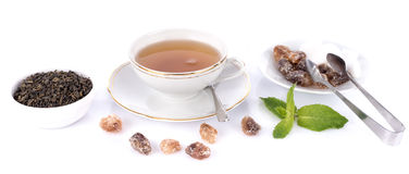 Cup of tea with green dry tea and crystal sugar Royalty Free Stock Image