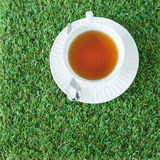 A cup of tea on the green grasses from top view Stock Photo