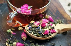 A cup of tea. green tea with flowers in a wooden spoon on a dark wooden table. green tea with flowers and dry fruit pieces. blend. Tea royalty free stock photography