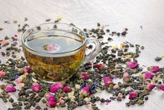 A cup of tea. green tea with flowers in a wooden spoon on a dark wooden table. green tea with flowers and dry fruit pieces. blend. Tea royalty free stock photos
