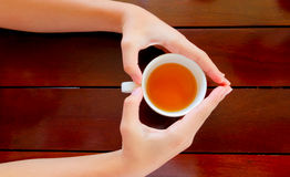 Cup of tea in hand, top view.  Royalty Free Stock Photography