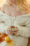 Cup of tea in the hands of a girl in a white sweater Royalty Free Stock Photography