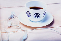 Cup of tea and headphones. On a wooden surface Royalty Free Stock Photo