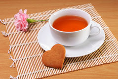 Cup of tea with heart shaped biscuit. White cup of tea with heart shaped biscuit and a flower Royalty Free Stock Images