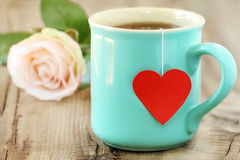 Cup of tea. With heart shaped teabag tag and a rose at the background Royalty Free Stock Images