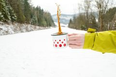 Cup of tea holding in woman hand. Winter background. Hot drink with foam. Snow and cold weather. Coffee break. Concept of drink in. Cup of tea holding in woman Stock Image