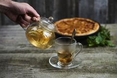 A cup of tea with homemade apple quince pie on rustic wooden background. A cup of tea with homemade apple quince pie on wooden background royalty free stock image