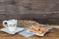 A cup of tea, homemade biscuits and wheat ears on a background of wooden boards. stock photography