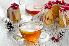 Cup of tea with Homemade glazed cranberry cake. On white wooden background with cones Stock Photography