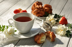 A cup of tea, homemade pastry, fresh ripe strawberries and delicate white flowers on a white wooden surface Stock Photo