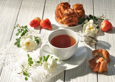 A cup of tea, homemade pastry, fresh ripe strawberries and delicate white flowers on a white wooden surface Royalty Free Stock Image