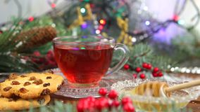 A cup of tea with honey and cookies, a branch of a Christmas tree in the snow, Christmas lights stock footage