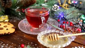 A cup of tea with honey and cookies, a branch of a Christmas tree in the snow, Christmas lights stock video