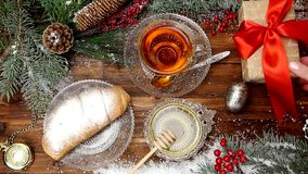 Winter tea A cup of tea with honey and croissant or cookies, a branch of a Christmas tree in the snow, Christmas lights stock video footage