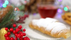A cup of tea with honey and croissant , a branch of a Christmas tree in the snow, Christmas lights stock video