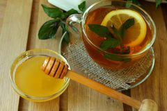 Cup of tea and honey jar. Cup of tea with lemon and mint and honey jar stock image