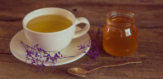 Cup of tea with honey in jar on the wooden table Royalty Free Stock Photography
