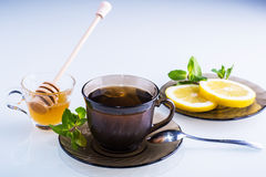 Cup of tea with honey and lemon slices. Cup of hot tea with honey, mint and lemon slices royalty free stock image