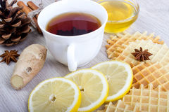 Cup of tea with honey, pinecone, badian, ginger, waffles and cinnamon Stock Photos