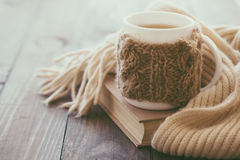 Cup of tea. Cup of hot tea with lemon dressed in knitted warm winter scarf on brown wooden tabletop, soft focus stock photo