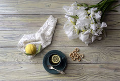 A cup of tea and irises. Rustic still life with a cup of tea and spring irises on a wooden table close-up Stock Photos