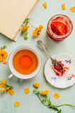 Cup of tea, jar with jam, book and yellow flowers Royalty Free Stock Photo