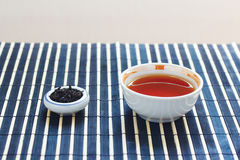 Cup of tea and jar of tea leaves on bamboo table Royalty Free Stock Photo