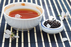 Cup of tea, jar of tea leaves and cherry blossoms Royalty Free Stock Images