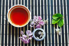 Cup of tea, jar of tea leaves and cherry blossoms Royalty Free Stock Photos